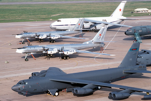 Two Tu-95 Bear bomber aircraft, center, and an AN-124 Condor transport aircraft of the Russian military, background, are parked on the flight line beside a B-52H Stratofortress aircraft of the 62nd Bombardment Squadron.  The Russian planes are on base as part of an exchange program proposed by Air Force Chief of Staff Gen. Merrill A. McPeak.