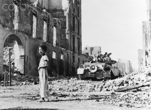 November 1956, Port Said, Egypt --- An Egyptian boy stands near a British tank amidst the rubble of destroyed buildings during the Suez Crisis. --- Image by © Hulton-Deutsch Collection/CORBIS