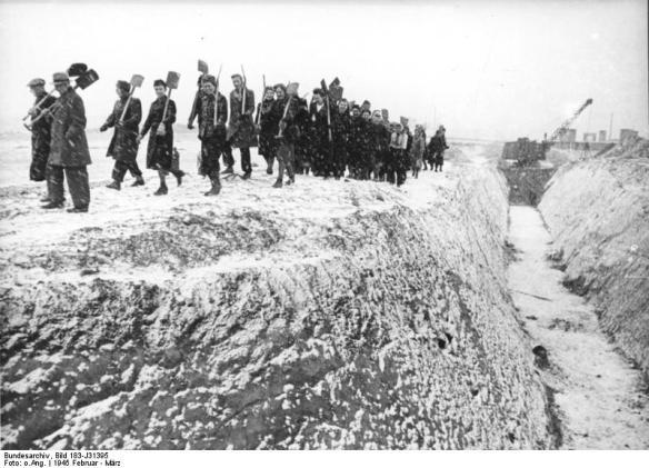 """ADN-ZB/Archiv Das faschistische Deutschland im II. Weltkrieg 1939-45 Berlin wird am 1. Februar 1945 zum """"Verteidigungsbereich"""" erklärt. Die Bevölkerung wird zum Bau von Straßensperrungen u.ä. befohlen. Betriebsangehörige, fast nur Frauen, im Schneetreiben auf dem Anmarsch zum Ausheben von Panzergräben am Stadtrand. Aufnahme Februar/März 1945 343-45"""